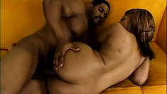 Asian Redd lies on the couch and sighs with pleasure as she gets spoon fucked hard