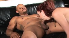 Fiery redhead rubs her clit while a big black stick punishes her ass